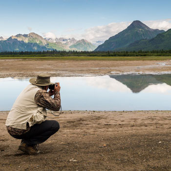 Alaska Bear Camp Photographer Squatting Down